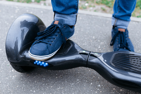 Leg men in blue sneakers and jeans standing on the blue gyroscooter platform, which is on the street. Start to using the electrical scooter, hoverboard, gyroboard or gyroscooter. 스톡 콘텐츠