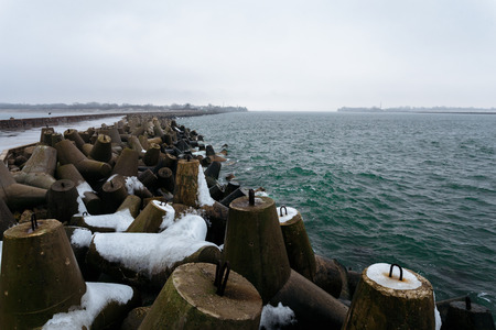 breakwaters: Many breakwaters with snow on the northern mall in the town of Baltiysk, Kaliningrad, Russia.