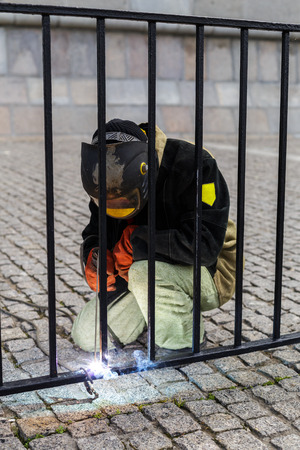 protective clothing: Welder welds on the fence railings. Wear protective clothing and a black mask