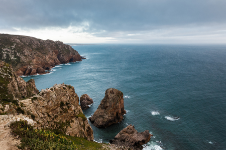 roca: View from Cape Roca in Portugal: the Atlantic Ocean and rocks in front of the sunset. Stock Photo