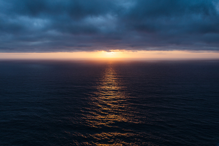 The sunlight pierced the dark blue clouds and lit up the Atlantic Ocean.