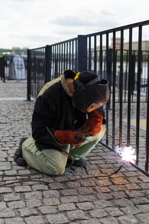 welds: Man in protective clothing and a welding mask welds a fence on the waterfront. Stock Photo