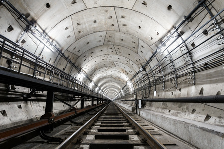 straight circular subway tunnel with a white lighting.
