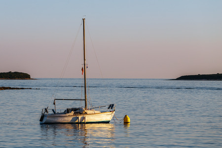 Lonely boat with a flat sail standing in the sea at sunset and the islands.