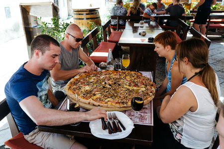 legendary: Porec, Croatia - July, 2016 - Group of people eat a large pizza at the legendary stari saloon.