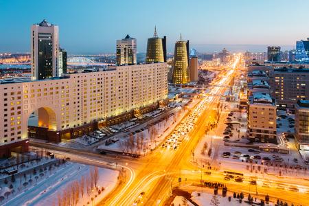 Vista desde arriba en una gran avenida que va al horizonte, un rascacielos dorado y una casa de ministerios en Astaná, Kazajstán.