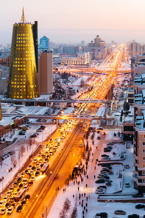 A view from above on a large avenue that goes down to the horizon, and a golden skyscraper of minestry in Astana, Kazakhstan.