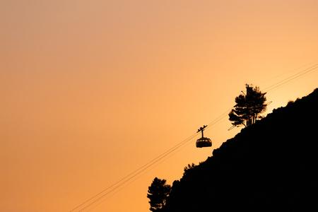 Cableway or ropeway to Mount Srdj in Dubrovnik, Croatia against the background of the orange sky. Reklamní fotografie
