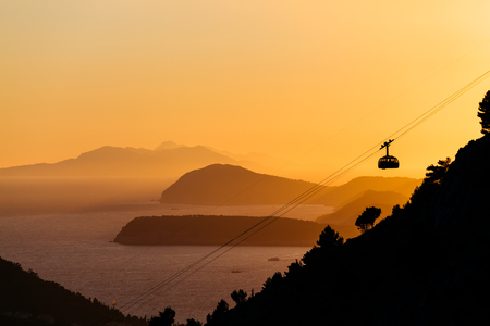ropeway: Cableway or ropeway to the mountain Srdj in Dubrovnik, Croatia against the background of a sunset over the islands in the sea