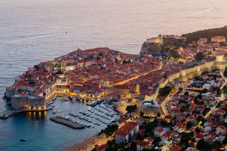 A view from above of Dubrovnik with the old part of the city during a bright colorful sunset.
