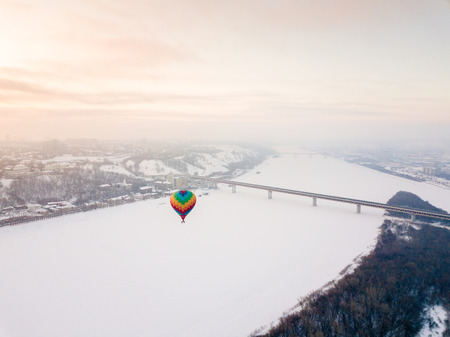 A colorful balloon flies over the city in winter. There is a bridge under it, snow is lying around it.