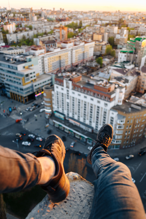 The guy is sitting on the edge of a tall building. He hung his legs with beautiful black sneakers over the city. High altitude and danger Reklamní fotografie