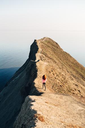 The girl goes to the ridge of Cape Chameleon in Crimea. Reklamní fotografie