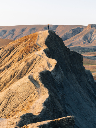 The girl is standing on the high ridge of Cape Chameleon in the Crimea.