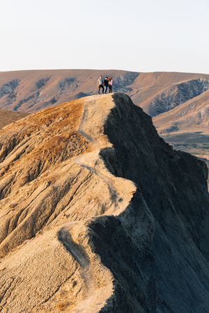 Three friends stand on the high ridge of Cape Chameleon in the Crimea.