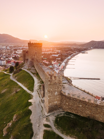 An old defensive fortress with towers in the city of Sudak in the Crimea at dawn from the height