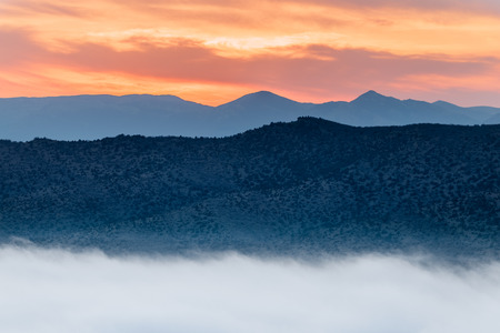 The thick fog fell below the mountains during the sunset.