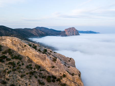 During the sunset in the mountains thick fog covered the rocks and the sea