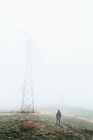 One man looks at huge wind farms, covered with fog, high in the mountains.