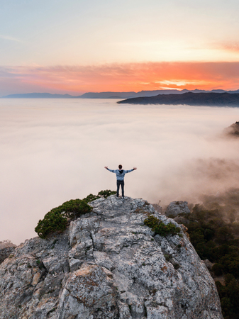 A man stands on the edge of a cliff above the dense fog that covered the sea, on Mount Kosmos in the Crimea. Stock Photo