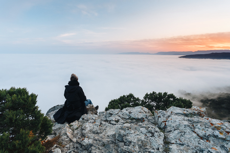The girl sits on the edge of the cliff above the dense fog that covered the sea, on Mount Kosmos in the Crimea.
