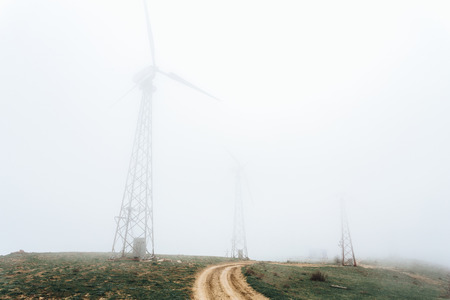 three huge wind farms, covered with fog, high in the mountains.