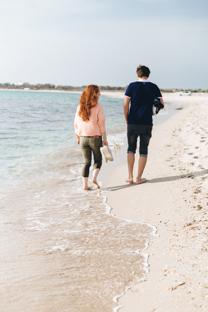 A young couple walking barefoot on the sand on an empty beach.