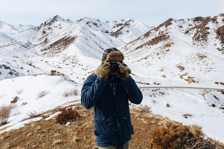 A cheerful traveler with a camera stands among the snow-capped mountains of Kazakhstan. Reklamní fotografie