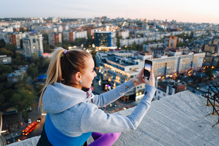 Young girl in sports uniform takes photos on the phone on the roof of a building over the city.