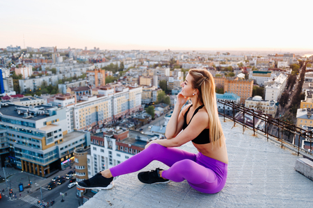 Young girl in sports uniform sits on the edge of the roof during sunset. Reklamní fotografie - 104036271