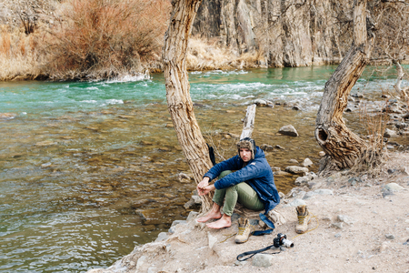 A traveler with a camera resting on the bank of a mountain stream. He dries his clothes and shoes