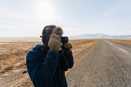 A cheerful traveler with a camera stands on the road in the Kazakh steppe completely alone. Reklamní fotografie