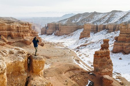 A cheerful traveler with a camera stands on the edge of the cliff in the Charyn canyon in Kazakhstan. Analogue of the American Grand Canyon. Reklamní fotografie - 106224063