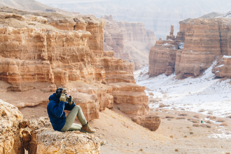 A cheerful traveler with a camera sits on the edge of a cliff in the Charyn canyon in Kazakhstan. Analogue of the American Grand Canyon. Reklamní fotografie - 106224067