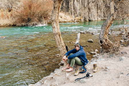 A traveler with a camera resting on the bank of a mountain stream. He dries his clothes and shoes Reklamní fotografie - 106224068