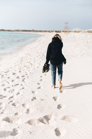 A young girl walks along an empty beach alone. Shoes in hand, footprints in the sand