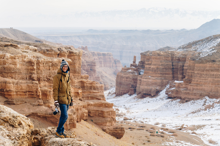 A cheerful traveler with a camera stands on the edge of the cliff in the Charyn canyon in Kazakhstan. Analogue of the American Grand Canyon. Reklamní fotografie - 106222275