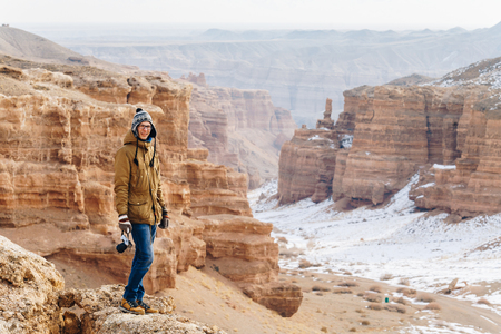 A cheerful traveler with a camera stands on the edge of the cliff in the Charyn canyon in Kazakhstan. Analogue of the American Grand Canyon. Reklamní fotografie - 106222274