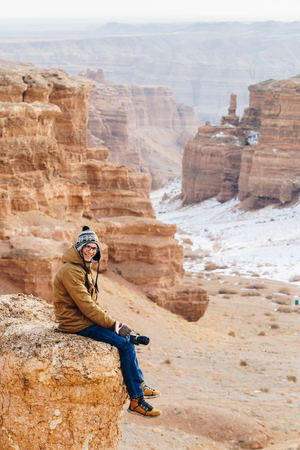 A cheerful traveler with a camera sits on the edge of a cliff in the Charyn canyon in Kazakhstan. Analogue of the American Grand Canyon. Reklamní fotografie - 106222278