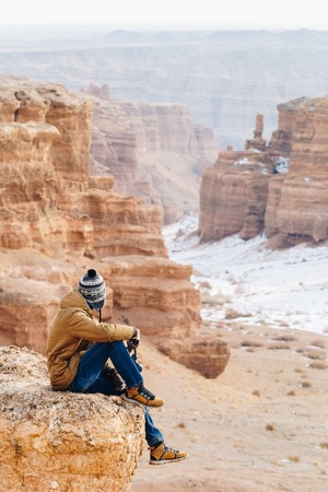 A cheerful traveler with a camera sits on the edge of a cliff in the Charyn canyon in Kazakhstan. Analogue of the American Grand Canyon. Reklamní fotografie - 106222279