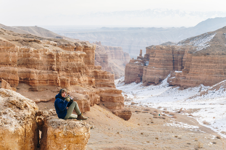 A cheerful traveler with a camera sits on the edge of a cliff in the Charyn canyon in Kazakhstan. Analogue of the American Grand Canyon. Reklamní fotografie - 106222281