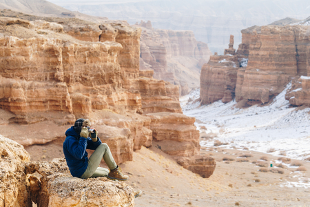 A cheerful traveler with a camera sits on the edge of a cliff in the Charyn canyon in Kazakhstan. Analogue of the American Grand Canyon. Reklamní fotografie - 106222283