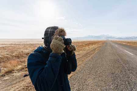 A cheerful traveler with a camera stands on the road in the Kazakh steppe completely alone. Reklamní fotografie - 106222280