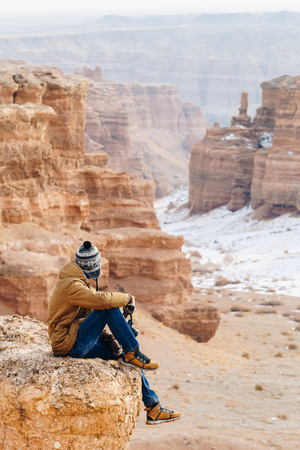 A cheerful traveler with a camera sits on the edge of a cliff in the Charyn canyon in Kazakhstan. Analogue of the American Grand Canyon. Reklamní fotografie - 104352210