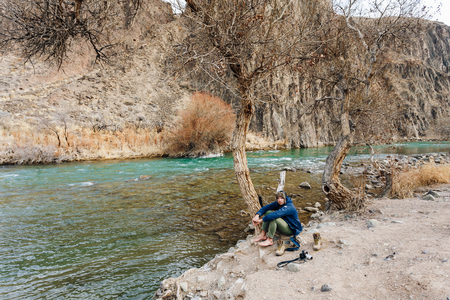 A traveler with a camera resting on the bank of a mountain stream. He dries his clothes and shoes Reklamní fotografie - 104354333