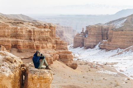 A cheerful traveler with a camera sits on the edge of a cliff in the Charyn canyon in Kazakhstan. Analogue of the American Grand Canyon. Reklamní fotografie - 104354335