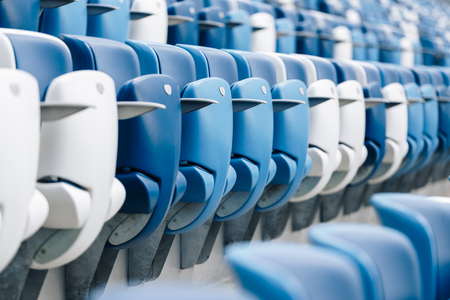 Multi-colored armchairs with numbers on a football stadium. Blue and white color Reklamní fotografie - 106222282