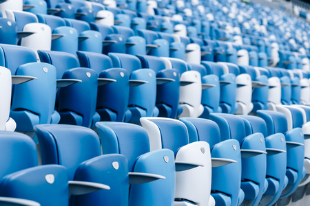 Multi-colored armchairs with numbers on a football stadium. Blue and white color Reklamní fotografie - 106222285