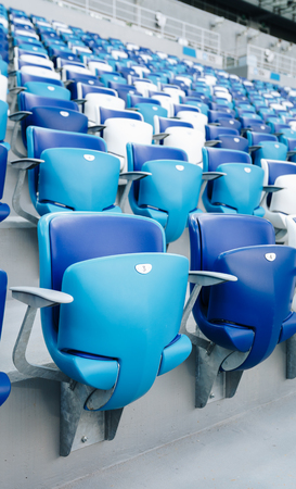 Multi-colored armchairs with numbers on a football stadium. Blue and white color Reklamní fotografie - 106224132