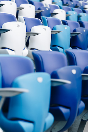 Multi-colored armchairs with numbers on a football stadium. Blue and white color Reklamní fotografie - 106224128